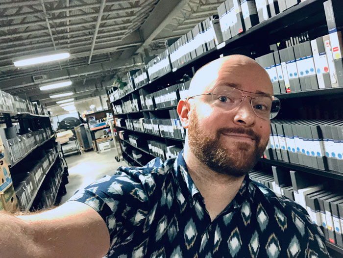 MSIS student Adam Hembree poses with donated collections in the basement of the Blount County Public Library, where he's doing a practicum this fall.